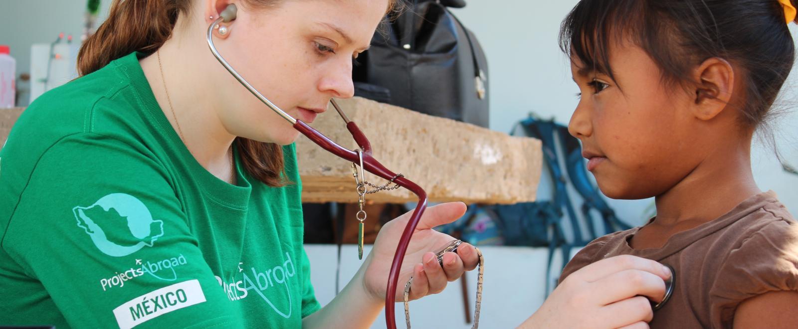 Joven voluntaria midiendo el pulso de una niña en unas prácticas médicas.